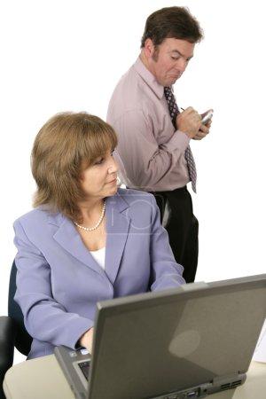 Photo pour Un collègue masculin d'espionnage sur un collègue féminin épaule et prendre des notes sur ce qu'il voit. isolé sur blanc. mettre l'accent sur les femmes. - image libre de droit