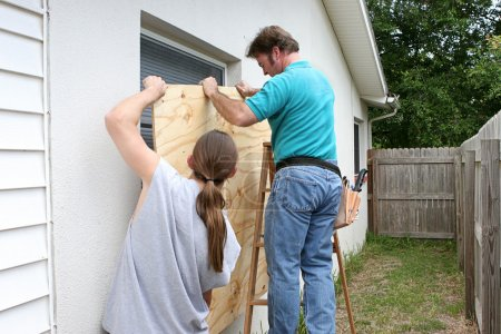 Photo for A father and son working together to install plywood over windows in preparation for a hurricane. - Royalty Free Image