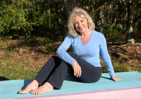 Photo for A beautiful, mature woman relaxing after doing yoga outdoors. - Royalty Free Image