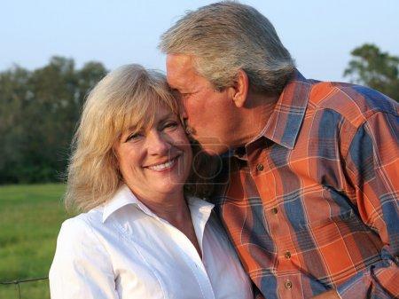 Photo pour Un homme séduisant qui donne sa belle épouse un baiser sur la joue - image libre de droit