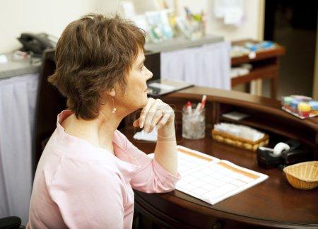 Photo pour Une vendeuse ennuyeuse assise à son bureau. Aucun client dans le magasin . - image libre de droit