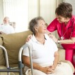 Senior woman in a nursing home, with a caring nurs...