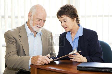 Photo pour Homme d'affaires senior signe un contrat avec l'aide d'une femme d'affaires mature. - image libre de droit