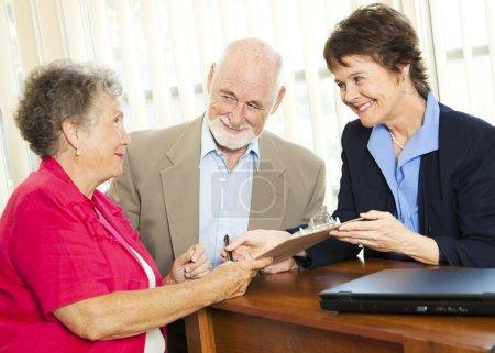 Photo pour Couple de personnes âgées travaillant avec un courtier ou un conseiller, signant des documents . - image libre de droit