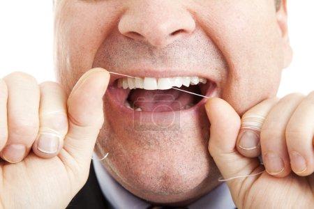 Photo pour Gros plan d'un homme passant ses dents au fil dentaire . - image libre de droit