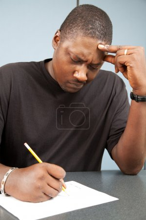 Photo for African-american adult education student struggles with test anxiety as he takes an exam. - Royalty Free Image