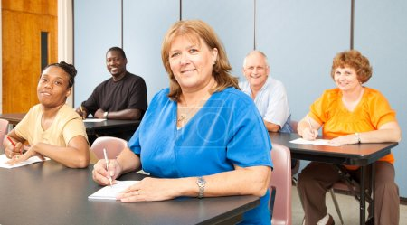 Photo for Mature woman in college, among a group of other adult students. Banner orientation. - Royalty Free Image