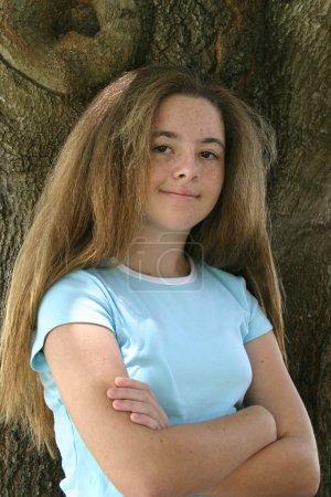 Photo pour Une adolescente aux cheveux très longs, appuyée contre un arbre les bras croisés . - image libre de droit