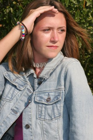Photo pour Une belle jeune fille dans une veste en Jean ombrage ses yeux du soleil. - image libre de droit