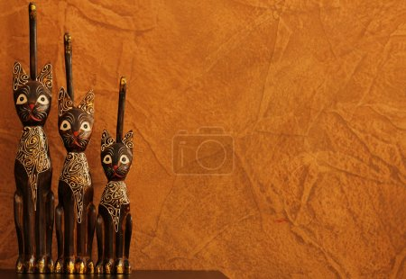 Three carved wooden cats against faux finish wall