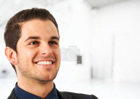 Photo pour Portrait d'un jeune homme d'affaires souriant. Fond lumineux flou . - image libre de droit