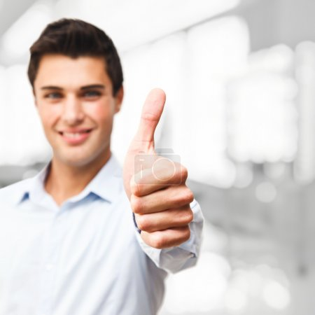 """Photo for Handsome guy showing """"OK"""" sign. Focus on thumb. - Royalty Free Image"""