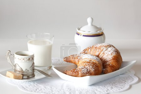 Photo for Continental breakfast with coffee, milk and croissants served on a table - Royalty Free Image
