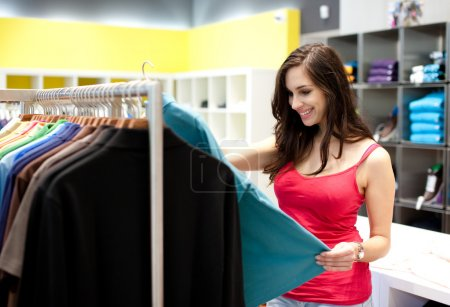 Beautiful young woman shopping in a clothing store. Shallow DOF.