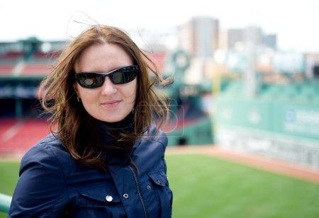 Photo pour Jolie jeune femme aux lunettes de soleil profite d'une visite au stade de baseball - image libre de droit