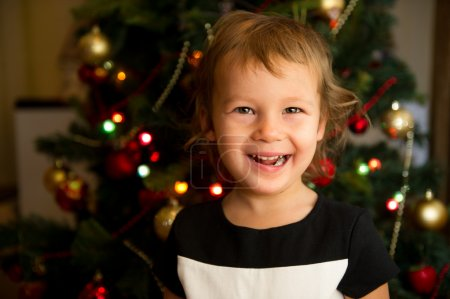 Portrait of little girl in front of Christmas tree