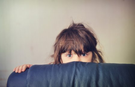 Little girl playing hide and seek behind the sofa