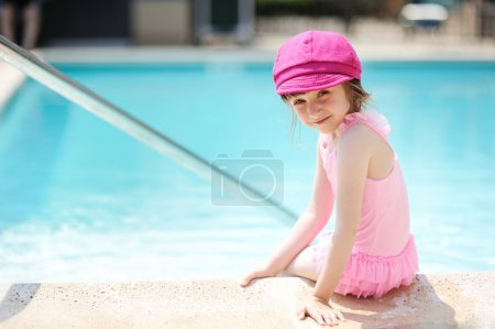 Little girl paddling her feet in a swimming pool