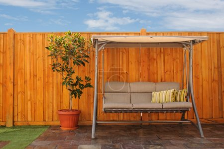 Photo for Outdoor Swing Chair and magnolia tree in an orange pot by the fresh timber fence. Backyard scene, Melbourne, Australia - Royalty Free Image