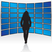 A woman standing in front of a wall of widescreen LCD or plasma TV screens