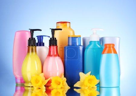 Photo pour Bouteilles de produits de santé et de beauté sur fond bleu avec réflexion - image libre de droit