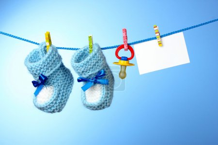 Baby booties, nipple and white card on a blue background