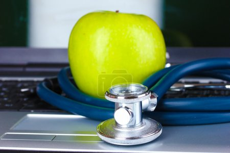 Medical stethoscope, apple and notebook