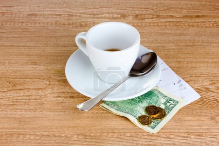 Empty cup of coffee with five dollars tip on wooden background.