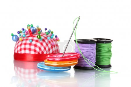 Bright sewing buttons, needle and skeins of thread isolated on w
