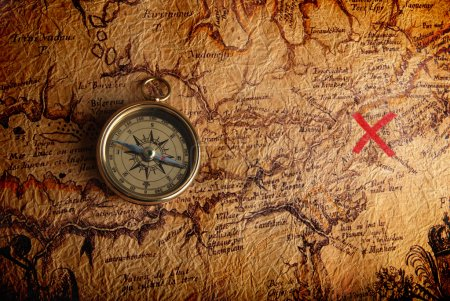 Old brass compass lying on a very old map showing ...