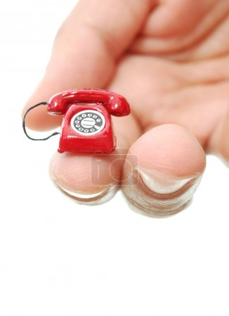 Photo for Miniature red telephone held by fingers of a hand - Royalty Free Image