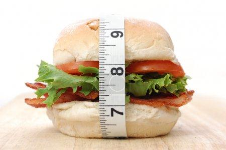 Photo pour Hamburger bacon, enveloppé d'un ruban à mesurer - image libre de droit
