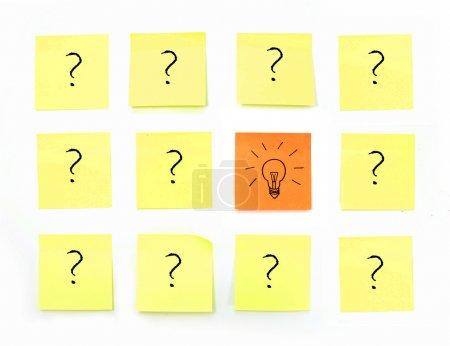 Photo pour Croquis d'une ampoule sur une note du pense-bête jaune entourée de nombreux points d'interrogation - image libre de droit