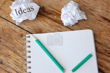 Photo pour Idées écrites sur un papier à côté d'un bloc-note froissé - image libre de droit