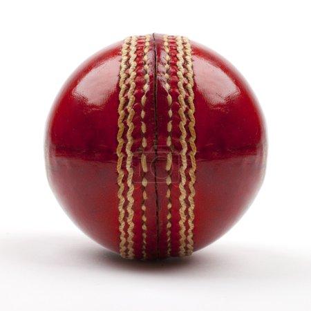 Photo pour Gros plan d'une balle de cricket rouge sur fond blanc . - image libre de droit