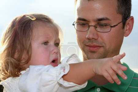 Photo for Closeup of a sad toddler girl in her father's arms, pointing and telling him what hapened, taken outdoors. - Royalty Free Image