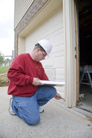 Photo pour Inspecteur à la maison à la recherche d'éventuels problèmes pour un acheteur potentiel, trouvé pourris armature en bois sur l'encadrement extérieur - image libre de droit