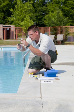 Photo for Service man checking chlorine, PH and other chemical levels in community pool - Royalty Free Image