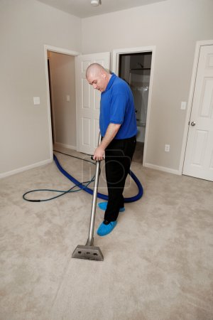 Photo for Man cleaning carpet with commercial cleaning equipment - Royalty Free Image