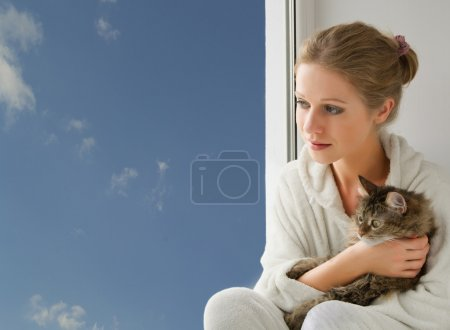 girl with a cat looking out