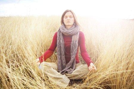 Photo pour Belle jeune femme méditant dans un champ ouvert dans l'herbe longue automne - image libre de droit