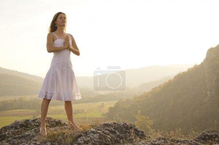 Photo pour Jeune femme debout dans la méditation au sommet d'une colline - image libre de droit
