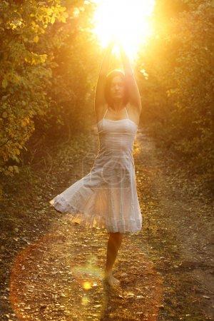 Photo pour Jeune femme en équilibre sur une jambe, méditant sur une piste de terre - image libre de droit