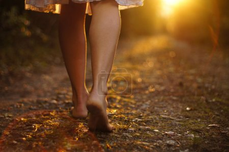 Photo for Young female legs walking towards the sunset on a dirt road - Royalty Free Image