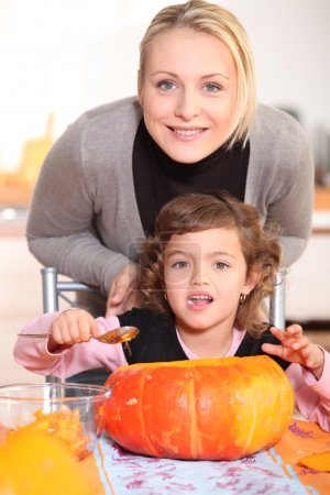Mother and daughter carving jack-o-lanterns