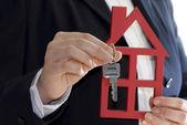 Asimiento de la mano una llave y una casa para la venta