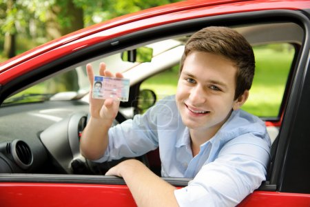 Photo for Teenager sitting in new car and shows his drivers license - Royalty Free Image
