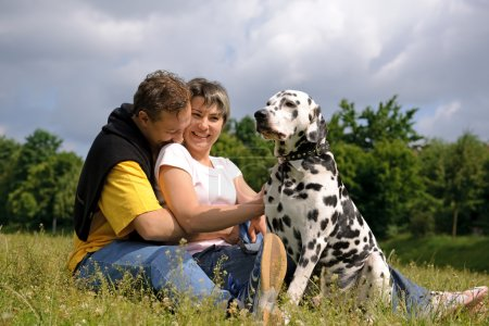 Photo for Loving couple with a Dalmatian outdoors - Royalty Free Image