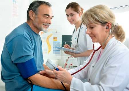 Photo for Patient is being observed by doctor - measuring blood pressure - Royalty Free Image