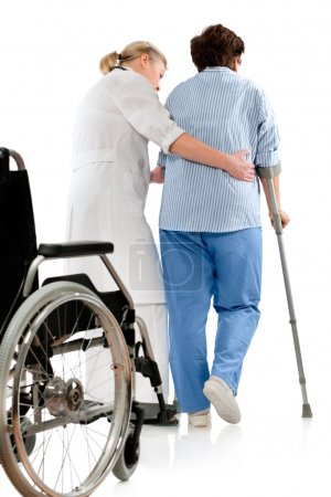 Photo for Nurse helps a senior woman on crutches - Royalty Free Image